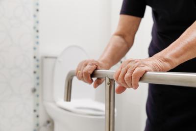 elderly man holding on handrail in bathroom