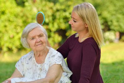 senior women with her caregiver in park